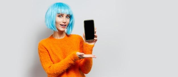 Ritratto in studio di giovane ragazza dai capelli blu, in possesso di uno smartphone, sul muro grigio.