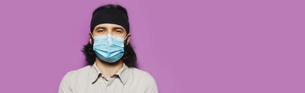 Ritratto in studio di giovane ragazzo bruna, con i capelli lunghi e la maschera protettiva medica, sullo sfondo del muro viola.
