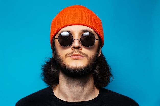 Ritratto in studio di giovane uomo sicuro di sé su sfondo blu. ragazzo con i capelli lunghi che indossa un cappello arancione, occhiali da sole rotondi e un maglione nero che guarda in alto.