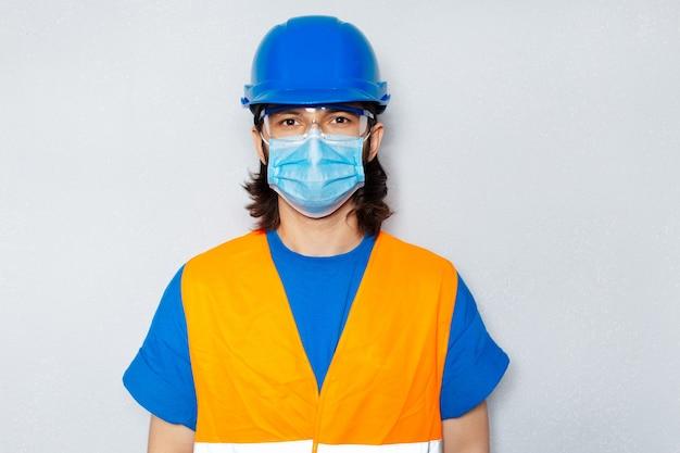 Ritratto in studio di giovane operaio edile con mascherina medica contro coronavirus e covid-19