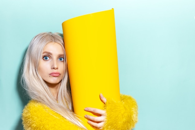 Ritratto dello studio di giovane ragazza eccitata che tiene grande rotolo di carta giallo nelle mani. sfondo di colore ciano, aqua menthe.