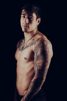 Ritratto in studio di un giovane uomo in forma con tatuaggi sulle braccia e sul busto su sfondo nero black
