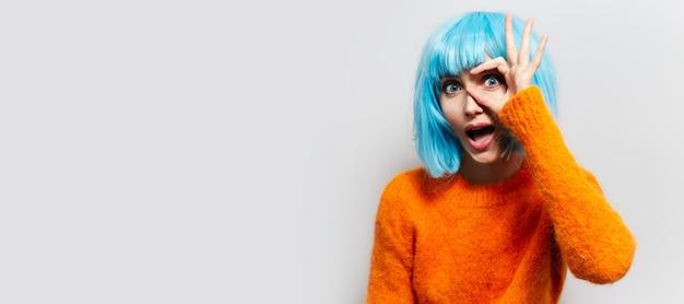 Ritratto in studio di giovane ragazza gesticolando segno ok su sfondo bianco. indossa un maglione arancione e una parrucca blu. vista panoramica del banner con spazio di copia.