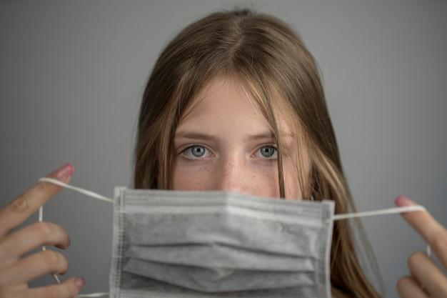 Ritratto in studio di una giovane ragazza che indossa una maschera facciale, primo piano, su sfondo grigio. epidemia di influenza, allergia alla polvere, protezione contro i virus. concetto di inquinamento atmosferico della città. copia spazio