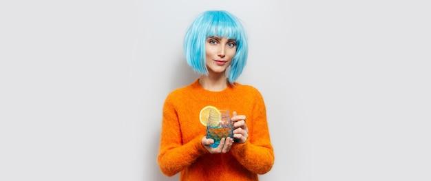 Ritratto in studio di giovane ragazza con parrucca blu, con in mano un bicchiere di acqua e limone.