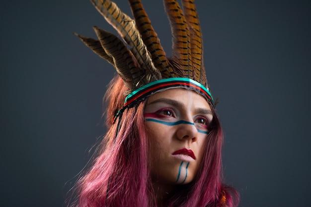 Ritratto in studio di una giovane ragazza con trucco e accessori indigeni