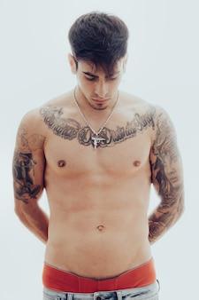 Ritratto in studio di un giovane uomo con tatuaggi e orecchini guardando in basso con un'espressione pensierosa con uno sfondo bianco.
