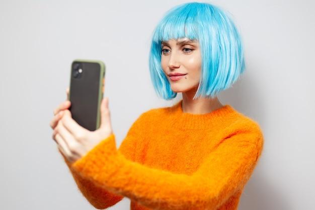 Ritratto dello studio di giovane ragazza graziosa, sorridente e prendendo la foto del selfie dallo smartphone su fondo di bianco; indossa un maglione arancione e un caschetto blu per capelli.