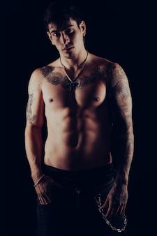 Ritratto in studio di un giovane uomo a torso nudo con tatuaggi in piedi con un atteggiamento maleducato.