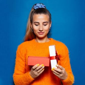 Studio ritratto di giovane donna in cerca di confezione regalo aperta sulla superficie blu