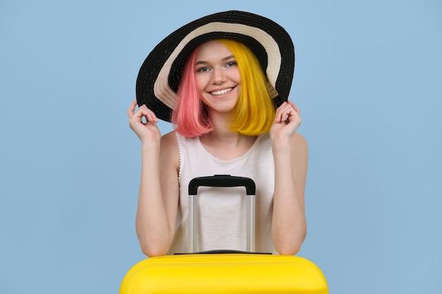 Ritratto in studio di giovane donna in cappello estivo con valigia. ragazza felice dell'adolescente su fondo colorato blu. estate, vacanze, trasporti, tempo libero, concetto di gioventù