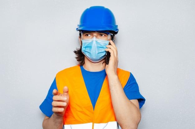 Ritratto in studio di giovane ingegnere operaio che parla tramite smartphone, indossando una maschera medica contro il coronavirus o il covid-19