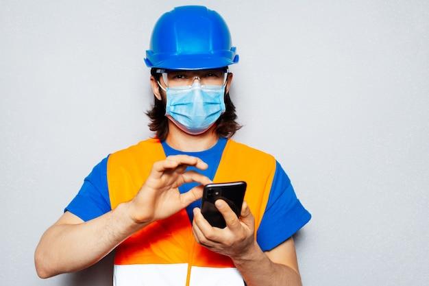 Ritratto in studio di giovane ingegnere operaio utilizzando smartphone, indossando maschera medica contro il coronavirus