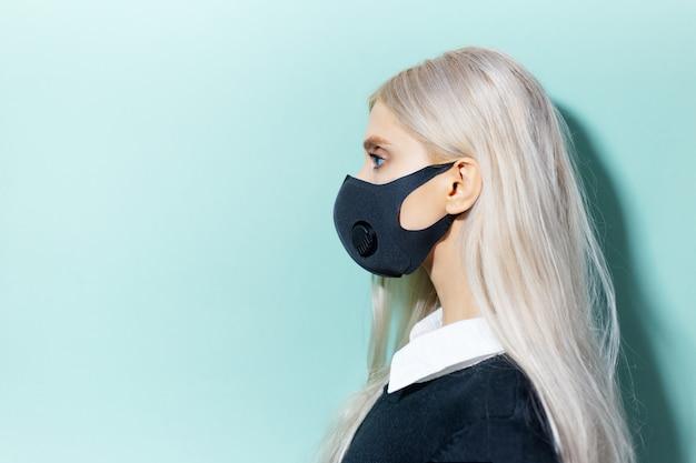 Ritratto di profilo in studio di giovane ragazza bionda che indossa una maschera respiratoria di colore nero, contro il coronavirus. sfondo di ciano, colore aqua menthe con spazio di copia.