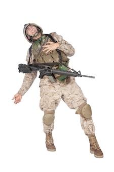 Riprese in studio del soldato dell'esercito in uniforme da combattimento e armatura, urlando, stringendo il petto, lasciando cadere le armi e cadendo dopo essere stato colpito a morte in uno scontro a fuoco militare marine viene colpito in battaglia