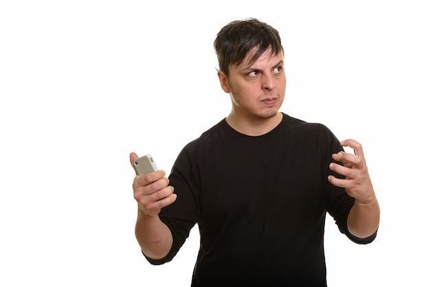 Studio shot di arrabbiato uomo caucasico hoding cellulare mentre thi