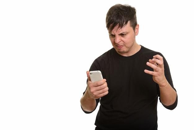 Studio shot di arrabbiato uomo caucasico hoding cellulare