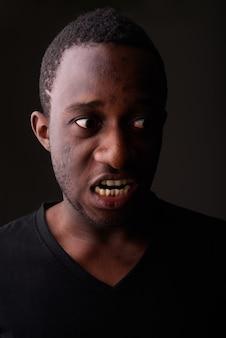 Studio shot di arrabbiato giovane africano nero uomo che grida nel buio r
