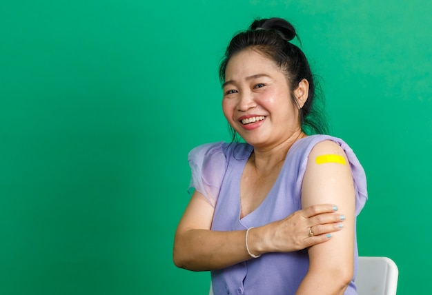 Studio shot asiatica felice di mezza età con capelli da donna paziente in abito di chiffon viola sorridente guarda la telecamera che mostra un cerotto giallo per bende dopo aver ricevuto il vaccino contro il coronavirus covid 19 su sfondo verde.
