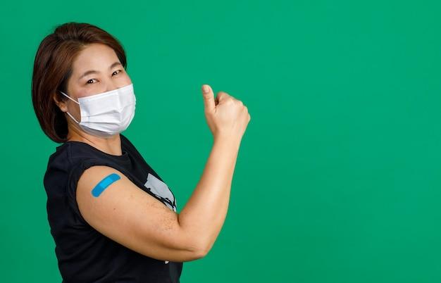 Studio shot di una paziente asiatica di mezza età, felice e sana, indossa una maschera facciale e guarda la telecamera che tiene il pugno alzato mostra i muscoli e l'intonaco della fasciatura blu dopo aver ricevuto il vaccino contro il coronavirus covid 19.