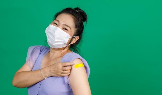 Studio scatto di una paziente asiatica di mezza età, felice e sana, indossa una maschera facciale e guarda la telecamera tenendo il pugno alzato mostra muscoli e cerotti gialli dopo aver ricevuto il vaccino contro il coronavirus covid 19.
