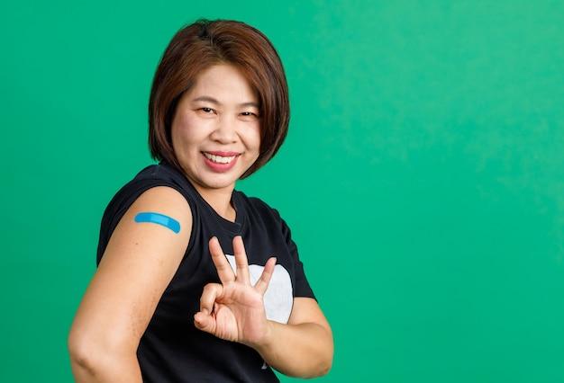 Studio shot di una paziente asiatica di mezza età seduta sorridente guarda la telecamera mostra il segno della mano ok e la benda di gesso blu sulla spalla dopo aver ricevuto la vaccinazione contro il coronavirus covid 19 su sfondo verde.