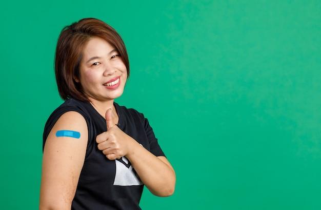Studio shot di una paziente asiatica di mezza età seduta sorriso guarda la telecamera mostra pollice in su e benda di gesso blu sul braccio dopo aver ricevuto la vaccinazione contro il coronavirus covid 19 in clinica su sfondo verde.