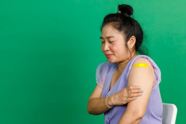 Studio shot di una donna asiatica di mezza età si siede sorridendo e mostra una benda di gesso gialla sul braccio dopo aver ricevuto la vaccinazione contro il coronavirus covid 19 dal medico in clinica su sfondo verde.