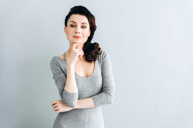 Studio shot di una donna attraente che tocca il suo mento. fiduciosa donna che guarda dritto nella telecamera
