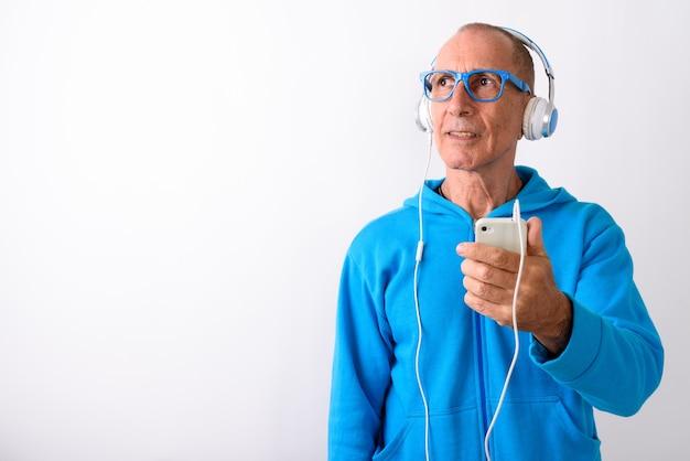 Studio shot di uomo anziano calvo tenendo il telefono cellulare mentre si pensa