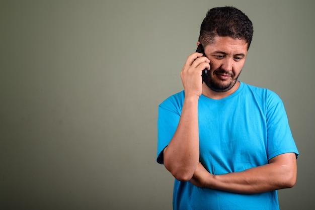 Studio shot di uomo barbuto che indossa la maglietta blu contro colorato