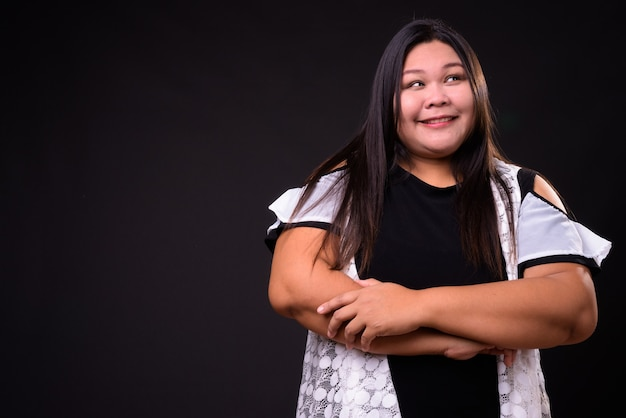 Studio shot di bella donna asiatica in sovrappeso su sfondo nero