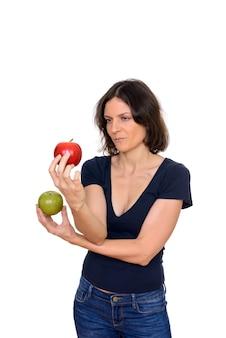 Studio shot di bella donna scegliendo tra mela rossa e verde isolato su sfondo bianco