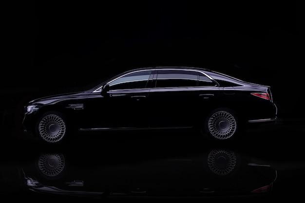 Colpo dello studio dell'automobile di lusso nera isolata sul nero