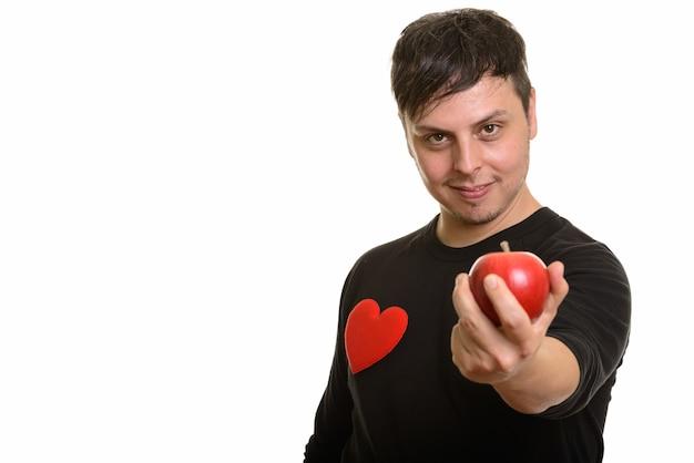 Studio shot di pazzo uomo caucasico che dà mela rossa pronta per va