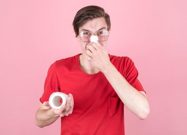 Studio girato da un giovane uomo con un fazzoletto e un rotolo di carta igienica. il ragazzo malato isolato ha il naso che cola. l'uomo sta facendo la medicina fredda. il nerd porta gli occhiali.