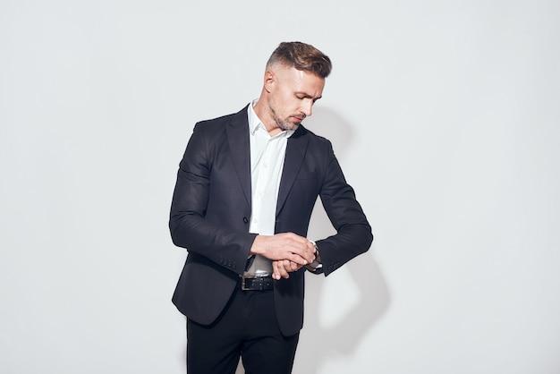 Studio shot di un bell'uomo d'affari barbuto in abito classico che guarda l'orologio in mano mentre si trova su sfondo grigio. concetto di tempo. aspetto aziendale.