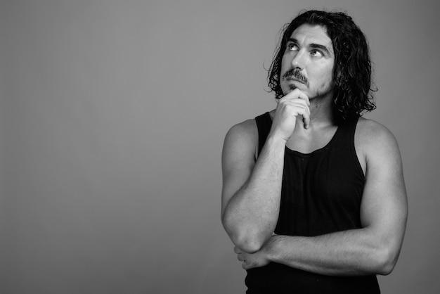 Studio shot di un bell'uomo macho con capelli ricci e baffi su sfondo grigio in bianco e nero