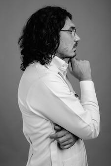 Studio shot di un bell'uomo medico con baffi su sfondo grigio in bianco e nero
