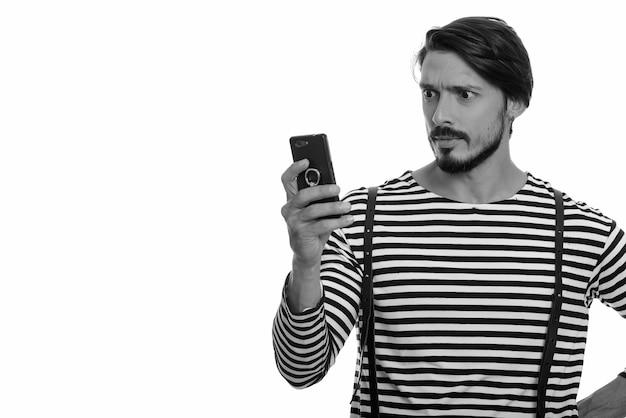 Studio shot di bell'uomo utilizzando il telefono cellulare cercando scioccato