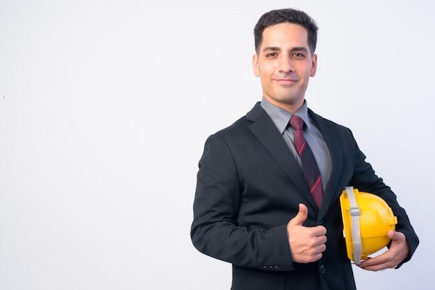 Studio shot di bell'uomo d'affari persiano in tuta come ingegnere con elmetto protettivo isolata contro bianco