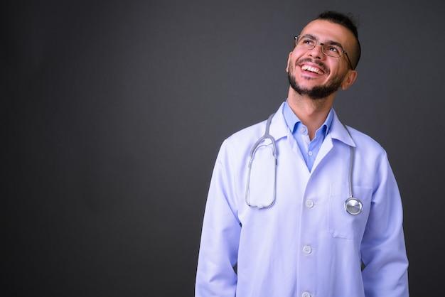 Studio shot di bel uomo turco medico contro uno sfondo grigio