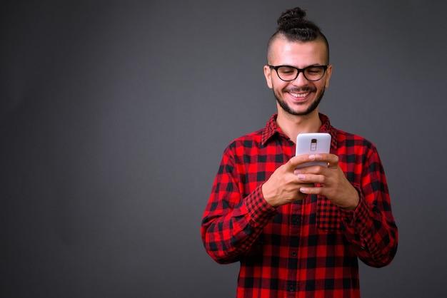 Studio shot di bel turco uomo che indossa occhiali da vista mentre si utilizza il telefono cellulare su uno sfondo grigio