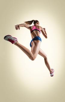 Lo studio di un atleta di salto in alto o di una donna in forma in azione isolato su sfondo grigio