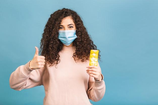 Studio shot di donna infetta con pillole in mano, signora che indossa la maschera protettiva