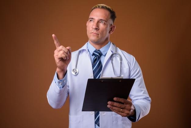 Studio shot di uomo medico tenendo appunti mentre si pensa