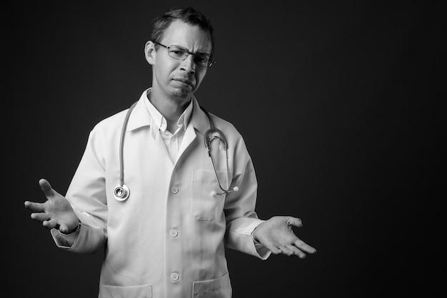 Studio shot di uomo medico che indossa occhiali contro il muro grigio in bianco e nero