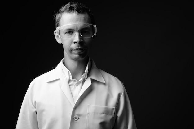 Studio shot di uomo medico che indossa occhiali protettivi contro il muro grigio in bianco e nero