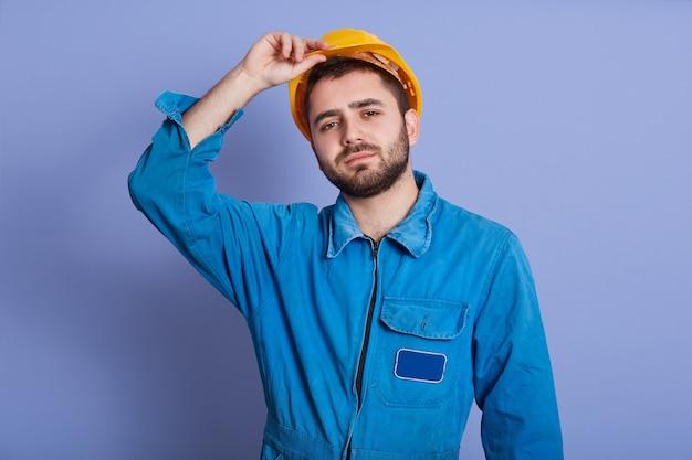 Lo studio ha sparato dell'uomo che indossa l'uniforme blu e il casco giallo della costruzione che esamina la macchina fotografica, tenendo la mano sul suo cappello duro, il tipo bello con la barba scura, sembra stanco dopo duro lavoro. concetto di costruzione.