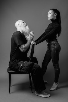 Studio shot di maturo uomo calvo barbuto e giovane bella donna asiatica insieme contro il muro grigio in bianco e nero